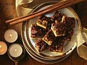 Pecan squares with cinnamon sticks on plate; candles