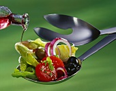 Pouring vinegar on to spoon over salad