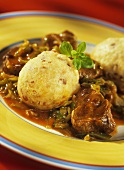 Cabbage goulash with bacon dumplings on yellow plate