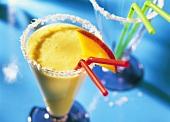 Mango & coconut shake with coconut flakes on glass rim