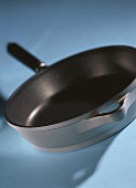 A braising pan on blue background