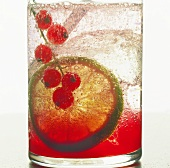 Fruit drink with redcurrants, lime and ice cubes