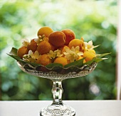 Apricots and white blossom in a crystal bowl
