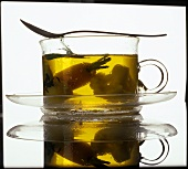 Bouillon with vegetables in a glass cup