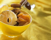 Various dried fruits in a yellow bowl