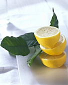 Three lemon halves with leaves on chopping board