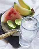 Limes, water melon, bananas and glass of ice cubes