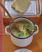 Provencal vegetable soup with fresh herbs in pot