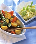Oven-baked vegetables with wooden spoon; Indian rice salad