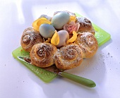 Easter wreath with roses & coloured eggs on chopping board