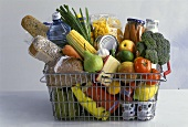 Wire basket with vegetables, fruit & various foodstuffs