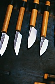 Four different sharp knives on black background