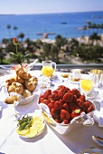 Holiday breakfast with fresh strawberries on terrace by sea