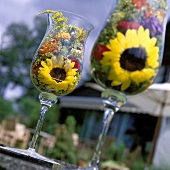 Summer flowers in glasses as table decoration in open air