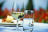 White wine glass and water glass on table in the open air