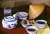 Tea in Chinese bowls with teapot, tea strainer etc