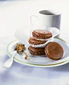 Chocolate macaroons in paper cases on plate; coffee