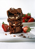 Pile of brownies with strawberries on white cloth