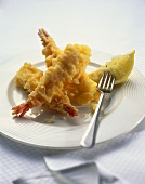 Fried shrimps with lemon wedge on plate