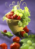 Green grapes, strawberries and raspberries in a yellow cup