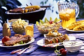 Grilled steak, kebab, corncobs & salads in front of grill