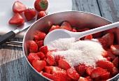 Making strawberry jam; stirring strawberries and sugar