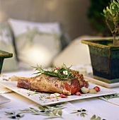 Leg of lamb with rosemary and garlic on table