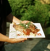Hands holding leg of lamb with rosemary and garlic on platter