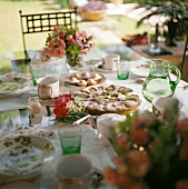 Table laid for coffee in open air with apple cake