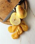Halved fresh pear beside dried pear halves