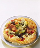 Pizza with ham, artichokes and olives on plate