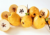 Whole and half quinces with drops of water