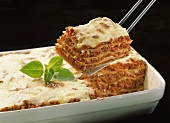 Lasagne with basil in baking dish, piece on server above it
