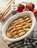Asparagus gratin with tomatoes in the baking dish