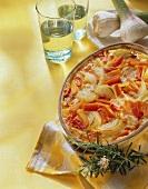 Baked ratatouille in baking dish; garlic; wine glasses