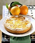 Orange & anise tart with icing sugar on plate; oranges