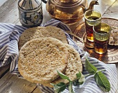 Algerian flatbread with sesame; tea; sprig of mint