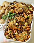 Braised rabbit with carrots and mushrooms in baking dish