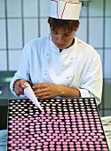 Female confectioner decorating chocolates with piping bag