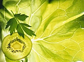 Kiwi slice and sprig of parsley on a lettuce leaf