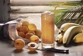 Aprikosen-Bananen-Drink, umgeben von frischen Früchten