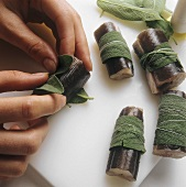 Wrapping sage leaves around pieces of eel