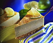 A piece of caipirinha cheesecake with limes on cake slice