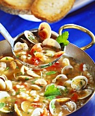 Mussel soup with barley on ladle and in soup pot