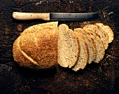 Sesame bread, partly sliced, on a wooden background