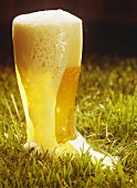 Foaming light beer in a boot-shaped glass