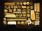 Many different types of pasta on dark wooden background