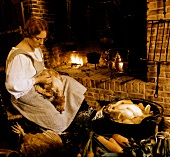 Country woman plucking chicken in front of fire