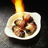 Flambéing bacon-wrapped plums on white plate