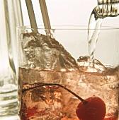 Cocktail mit Tonic aufgiessen